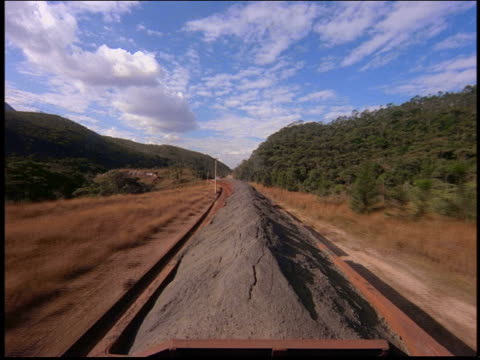 Train point of view in countryside on car full of iron ore / Brazil
