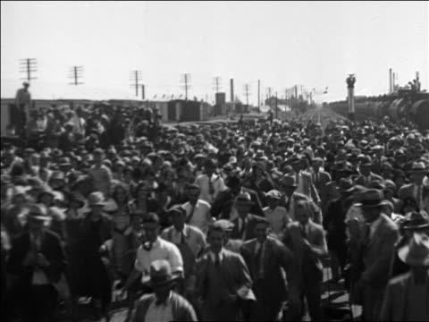 b/w 1928 train point of view men chasing after train during al smith's campaign / documentary - 1928年点の映像素材/bロール
