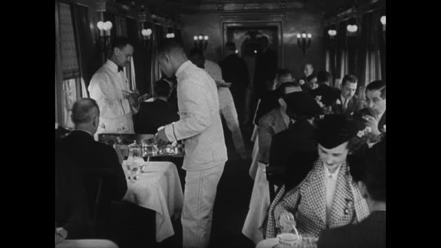train porter w/ dinner gong ha ms passengers in club car ms people in dining car tables ms children receiving child's menu cu girl looking at menu ms... - anno 1936 video stock e b–roll