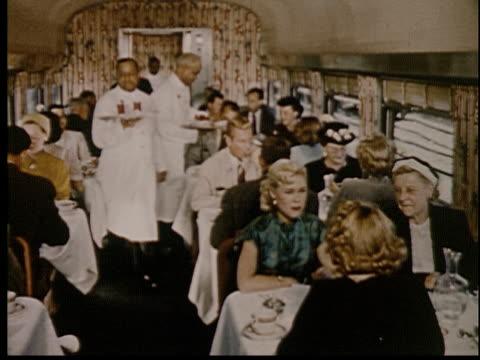 vídeos y material grabado en eventos de stock de 1955 ms train porters serving people in dining car of train - maletero