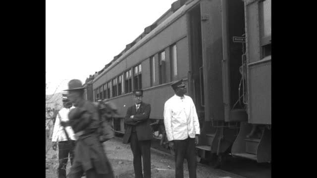 train pulling away with us soldiers visible in windows of train cars / two shots of soldiers carrying rifles stepping off train as conductor and... - 1920 1929 stock videos & royalty-free footage