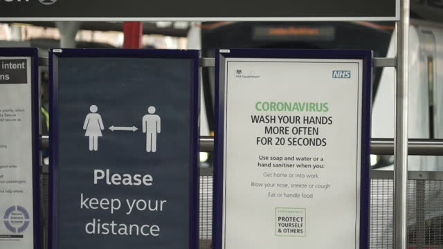 train pulling into platform at euston station, coronavirus posters on platform - pulling stock videos & royalty-free footage