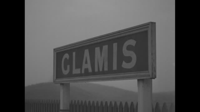 Train pulling into station / sign says Glamis / train station workers and luggage waiting for train to stop / Duchess of York daughters Elizabeth and...