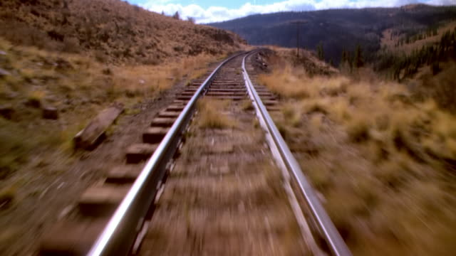 pov train riding through rocky mountains, colorado, usa - bahngleis stock-videos und b-roll-filmmaterial