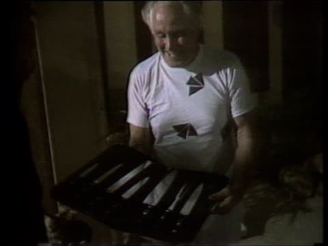 Train robber Ronnie Biggs accepts gift from friend at party marking 20th anniversary of his escape from prison July 1985