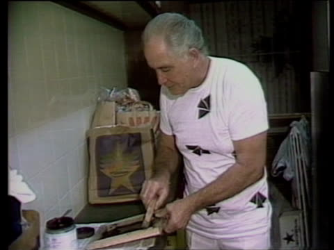 vidéos et rushes de train robber ronnie biggs creates mock prison tshirts during celebration party marking 20 years since escaping prison july 1985 - cadrage aux genoux