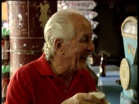 train robber ronnie biggs holds glass of beer while laughing and joking at bar november 1997 - 脱獄する点の映像素材/bロール