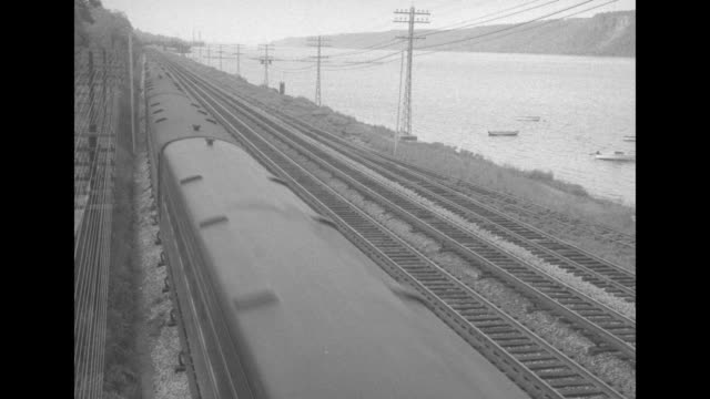 train rolling down track away from camera / two shots of train rolling down track alongside hudson river towards and past camera / two shots of train... - hochbahn passagierzug stock-videos und b-roll-filmmaterial