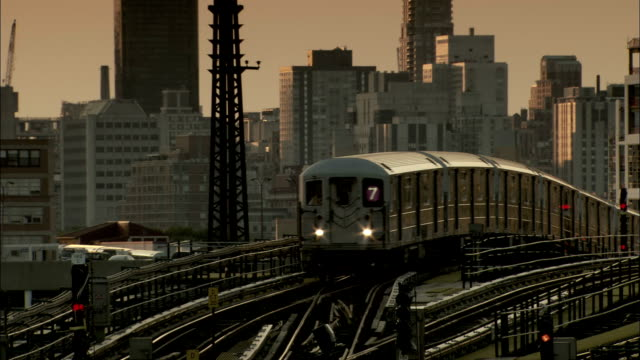 A train rounds a corner near skyscrapers in New York City. Available in HD.