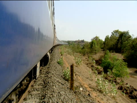 Train running along track through arid countryside Goa