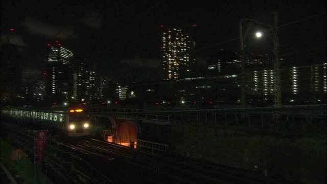 train running between the tamachi station and the shinagawa station on the yamanote line at night - minato ward stock videos & royalty-free footage
