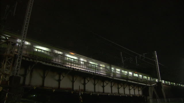 train running on the overbridge between the shinagawa station and the osaki station on the yamanote line at night - minato ward stock videos & royalty-free footage