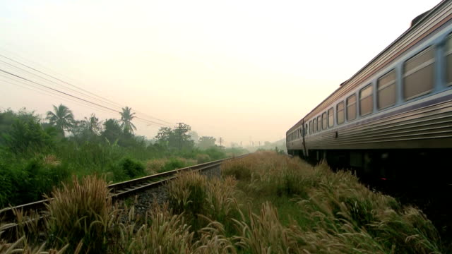 train running over rural railway at sunrise or in the morning - railway track stock videos & royalty-free footage