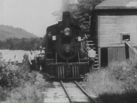 american narrow gauge. train sheds; rural tracks; rail fans; oiling; pushing turntable; train details; freight train; ball signals; small town stations; motor trains; train plow in snow; along mountain edge; child looks out; canyon; mail/passenger train. - 機関車点の映像素材/bロール