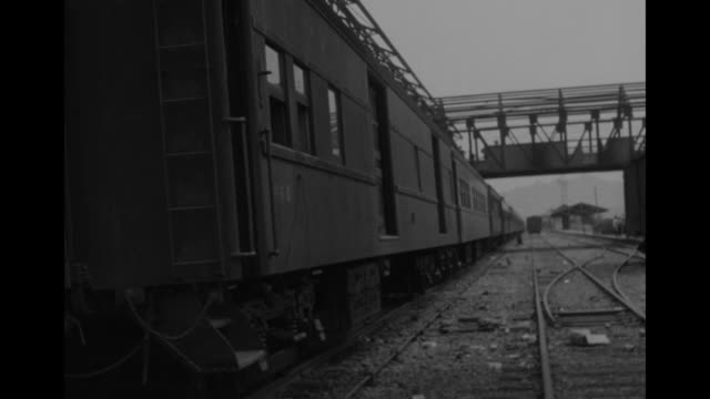 ls train sits stationary on track as another passes thru covered bridge over tracks in background / ms us serviceman writes letter while seated... - 停戦点の映像素材/bロール