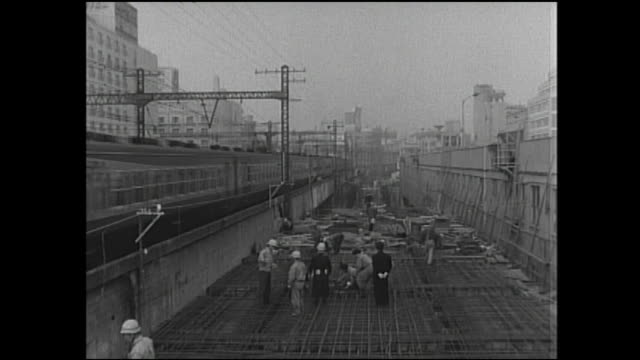 vídeos de stock, filmes e b-roll de a train slowly passes a construction site of the tokaido shinkansen. - 1960