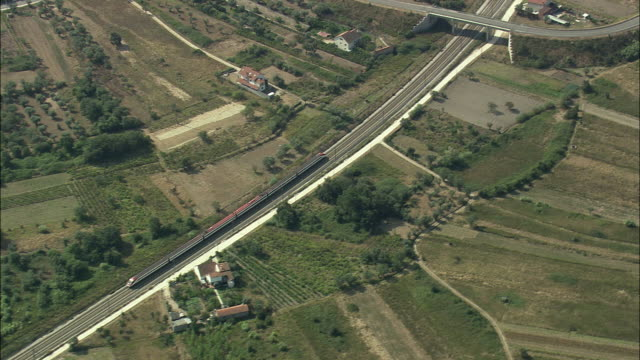 aerial ws ts train speeding on track through village / pombal, leria, portugal - moving past stock videos & royalty-free footage