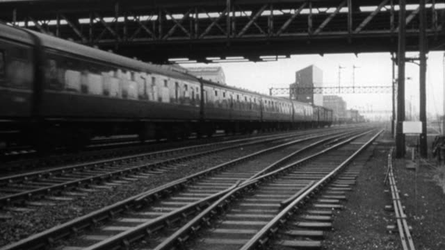 vídeos de stock, filmes e b-roll de 1965 montage train speeding on tracks with city in background, cars stalled on rural highway, train stations rushing past from inside train, with dr. beeching narrating / united kingdom - narrating