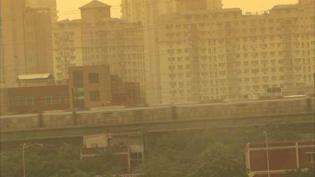 a train speeds through the city past skyscrapers. available in hd. - smog stock videos & royalty-free footage