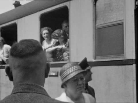train station a train filled with daytrippers waiting for departure summertime camera pans along train to end up on houses in the background a few... - anno 1938 video stock e b–roll