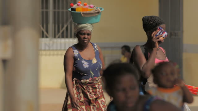 train station platform luanda women are waiting for a train on a platform one woman walking across the frame is carrying a large plastic basket with... - パレオ点の映像素材/bロール