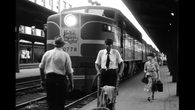 vidéos et rushes de train station platform, people, porters walking along platform next to train engine labeled 'new york new haven and hartford'. people walking along... - locomotive
