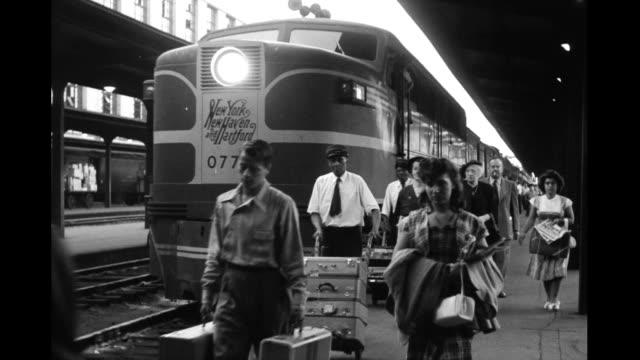 Train station platform people porters walking along platform next to train engine labeled 'New York New Haven and Hartford' People walking along...