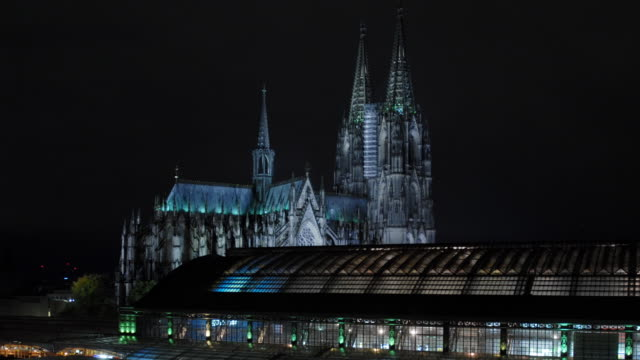 t/l, ws, train station with cathedral in background at night, cologne, north rhine-westphalia, germany - kathedrale stock-videos und b-roll-filmmaterial