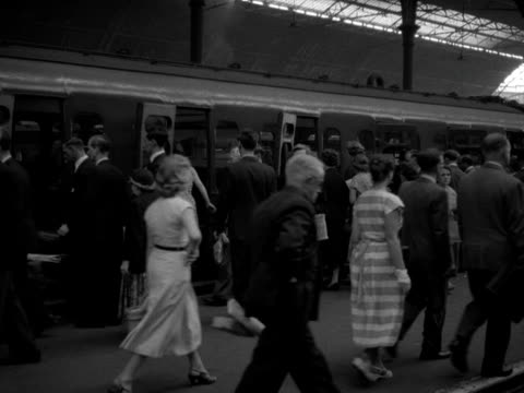 A train stops at a platform at Victoria Station and passengers get off and on 1958