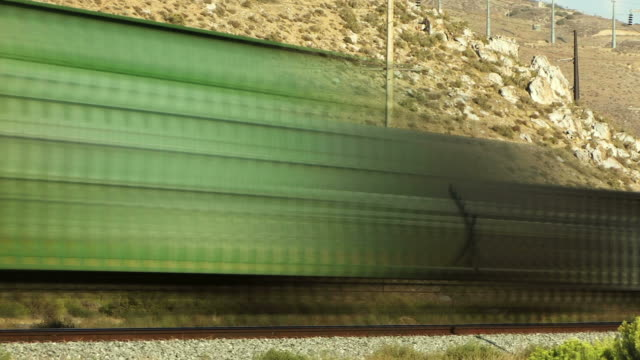a train streaks past rocky hills. - digital enhancement stock videos & royalty-free footage
