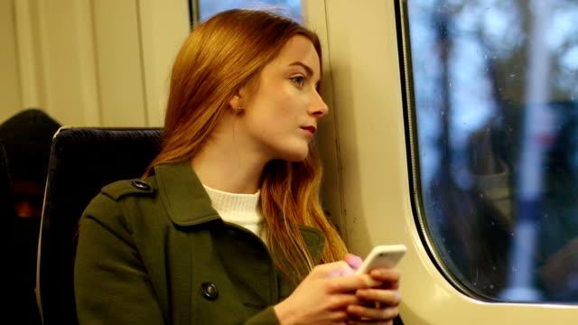 attraktive junge frau in einem zug über ihr handy. - passenger train stock-videos und b-roll-filmmaterial