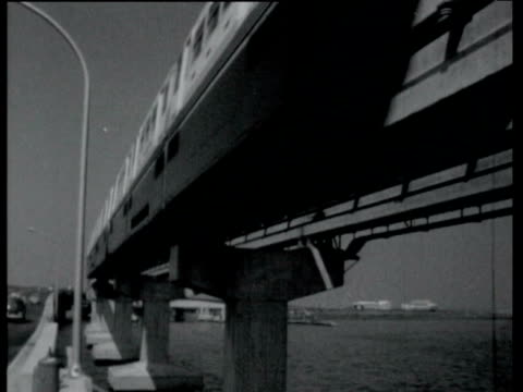train towards and past on monorail over tokyo bay / interior of monorail train carriage / train conductor driver in cab of train / pov shot through... - 1964年点の映像素材/bロール