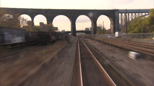 train tracks extend through an aqueduct, an underpass, and through an urban neighborhood. - aqueduct stock videos and b-roll footage