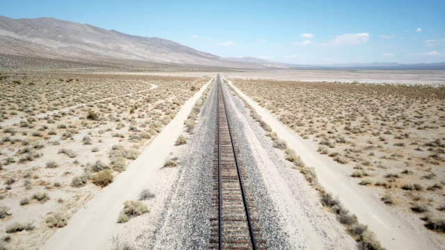 Train Tracks Extending Into Distant Desert Under Sun