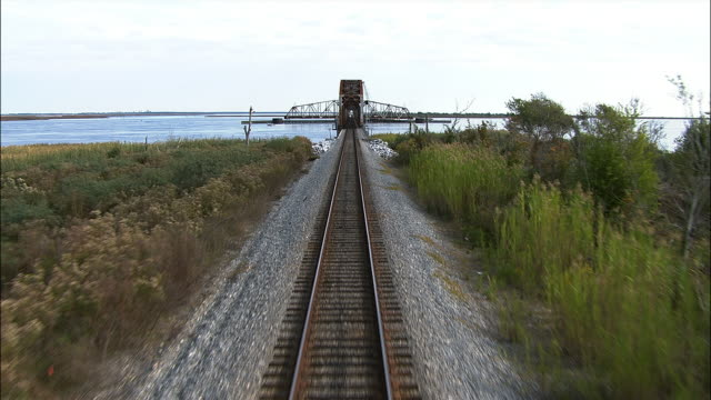 train tracks lead to an open swing bridge. - swing bridge stock videos & royalty-free footage