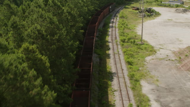 WS TU AERIAL POV Train tracks passing through forest area with old empty train containers on track / Myrtle Beach, South Carolina, United States