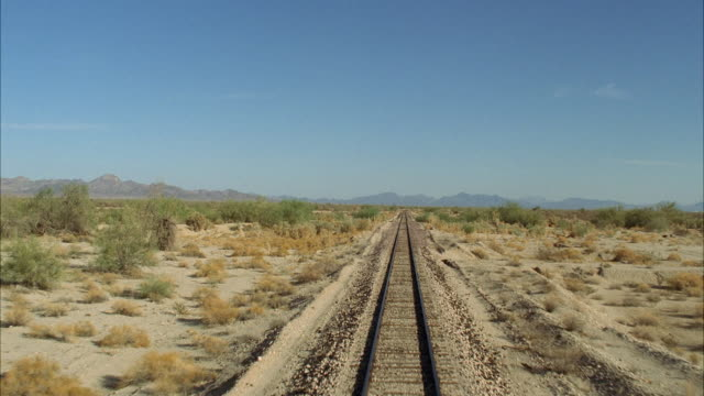 ws pov train tracks through barren steppe - bahngleis stock-videos und b-roll-filmmaterial