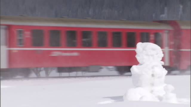 a train travel by a snowman. - snowman stock videos & royalty-free footage