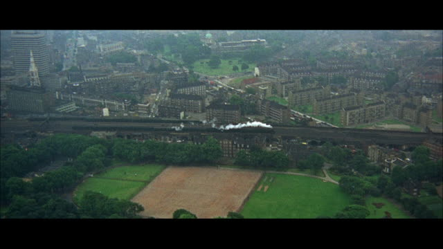 1966 aerial ws train traveling through city suburbs / london, england - 1966 stock videos & royalty-free footage