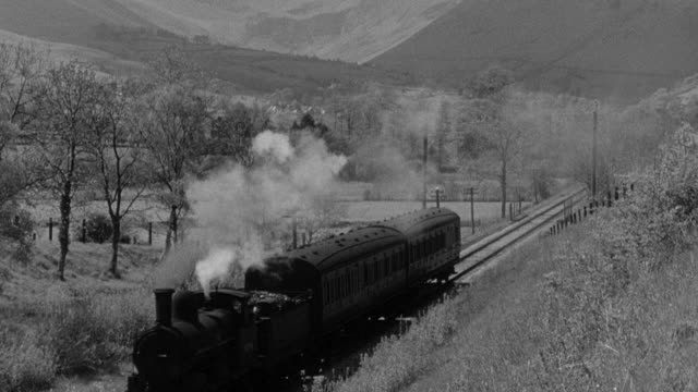stockvideo's en b-roll-footage met montage train traveling through the countryside and over a bridge in the highlands, and a freight train slowly moving over the tracks in west cornwall / united kingdom - stoomtrein