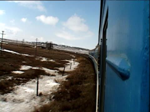 Train travelling through snow covered wilderness Kazakhstan