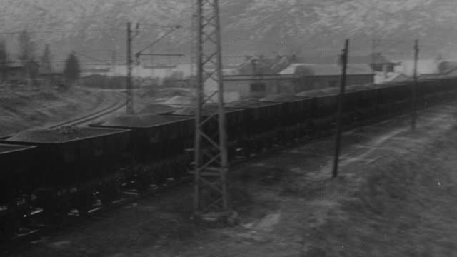 MONTAGE Train travels along tracks with iron ore in wagons, iron ore is dumped into large containers, ships are traveling on the water /Great Britain