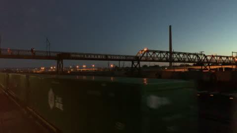 stockvideo's en b-roll-footage met een trein reist onderaan sporen onderaan een wandelbrug in laramie, wyoming bij zonsondergang/zonsopgang - wyoming