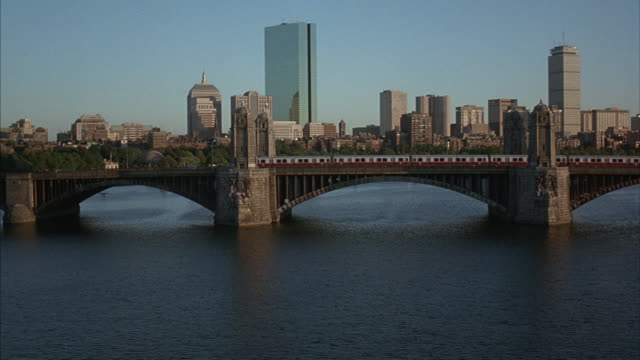 a train travels over a bridge on the charles river in boston. - charles bridge stock-videos und b-roll-filmmaterial