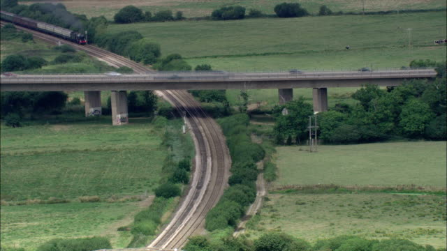 a train travels through lush farmlands and passes under an overpass. available in hd. - locomotive stock videos & royalty-free footage