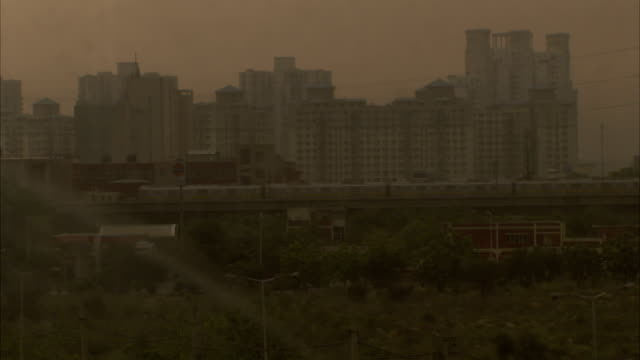 A train travels through the a hazy city on an overpass. Available in HD.