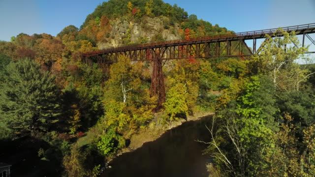 train trestle crossing river amid fall foliage - ニューパルツ点の映像素材/bロール