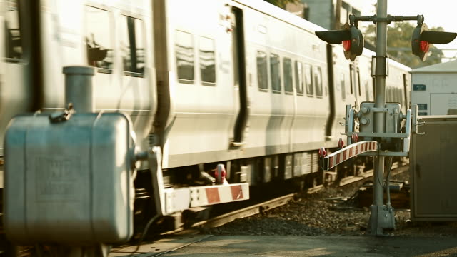 train zooming past railroad crossing arms - long island video stock e b–roll