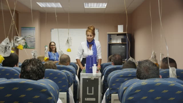 trainee in aviation cabin crew class practicing beverage service with female instructor in background looking on, RED R3D 4k