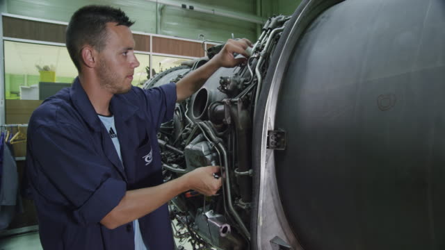 vídeos de stock, filmes e b-roll de ds zo trainee in aviation mechanic training facility working on a turbofan jet engine - indústria aeroespacial